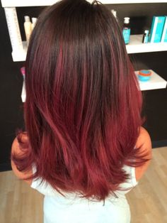 Red balayage ombre hair is darker at the roots before giving way to a distinct tone.