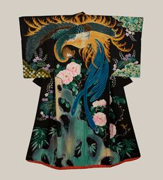 A vivid and remarkable silk wedding kimono features a masterful depiction of a phoenix, paulownia and peony flowers. The phoenix is the female counterpart of the male dragon and its varied colored feathers represent the traditional virtues of truthfulness, propriety, righteousness, benevolence and sincerity. The peony, known as the flower of riches and honor, is an emblem of wealth and distinction. It symbolizes prosperity, happiness, peace and is an emblem of love and affection.