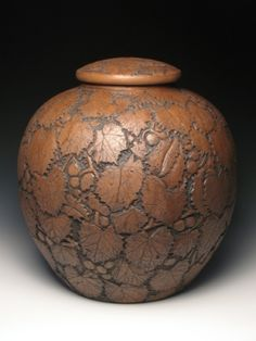 Covered Jar by Brent Smith. Constructed out of clay from Cauble Creek Vineyard. The carving is of Muscadine vines.