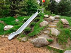 An embankment slide is built into a constructed hill at an elementary school as shown here in Glens Falls, N.Y. The embankment slide is safer than tower slides with ladders. Scattered boulders, random dirt steps, rough terrain, and varied plantings add to the rich textures and varied experiences on Natural Playgrounds.