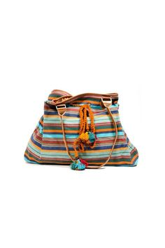 "This roomy, durable, fair trade carry-all is perfect for the beach or a picnic. Made from a unique combination of art forms and sustainable materials. Hand-woven exterior in a gorgeous array of bohemian tones with leather handle. Colorful rope cord accented with tassels and wooden beads ties on outside of bag for adjustable closure. Interior is lined with block printed fabric and has two open pockets plus one zippered pocket. Dimensions: 19"" x 6"" x 14' with 14' drop.   Boho Carry-All Bag by…"