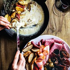 Raclette (Melted Cheese) | No dish epitomizes cozy elegance quite like raclette, a hunk of cheese melted in front of a fireplace and the gooey top layer scraped off and eaten with boiled potatoes, pickles, bread, and sliced meats.