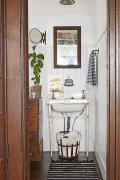 The couple made the home's lone bathroom feel airier by ripping out the existing vanity and replacing it with an antique wall-mounted sink with cast-iron legs. An old metal basket lined with linen houses extra rolls of toilet paper. Baños Shabby Chic, Wall Mounted Sink, Metal Baskets, Old Farm Houses, Home Interior, Interior Design, Bathroom Interior, Interior Decorating, Decorating Ideas