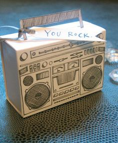 Hand drawn boombox letterpress in a soft black ink on smooth white paper. Slidebox opens to hold a small favor. Handwritten 'You Rock' tag with silver ribbon tied to handle.