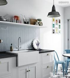 modern Kitchen by Equipe Ceramicas. Large porcelain sink and a simple single kitchen shelf and pendant lamps.