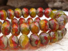 Ruby red and yellow translucent glass beads. Great fall color beads!    Size: 6x8mm  Quantity: 1 strand (25 beads)    1029/RON