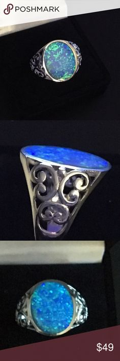 925 Sterling with lab created opal Last one! Lovely flat oval lab created opal flashes lovely bright blue and green fire and is inlaid in rhodium plated 925 Sterling silver with an intricate scroll design on the sides.  Stone is thin and translucent, flush mounted in setting. Jewelry Rings