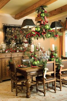 A coupling of green balls and red bells hangs from the ceiling & each chair holds its own stocking ornament.