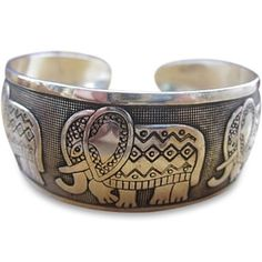 A beautifully crafted family of Five Thai Elephants on this brushed silver open Bangle Bracelet is a sight to see. This Elephant family is strong and sweet. They are adorned with finery and decorative rugs on their backs. Each of them has upright trunks, curved tusks and they are following each other. Each elephant is seen with his or her best foot in forward walking motion. It looks like they are walking in a walk-a-thon for an Elephant festival, and who knows they just might be on their…