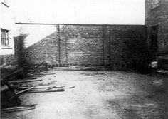 """Auschwitz, Poland, Execution wall between Block 10 and Block 11 in the camp, Postwar. Block No. 11 was known by the prisoners of Auschwitz as """"the death block."""" Here, the SS placed male and female prisoners from all over the camp who were suspected by the camp Gestapo for any small infraction. They were subjected to brutal interrogation that usually ended in a sentence of death by being shot or hanged."""
