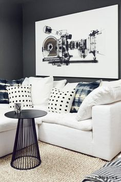 A Living room with gray walls,  a white sofa, and an oversized black and white painting
