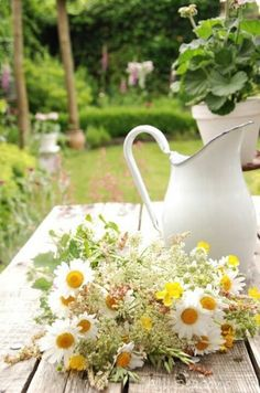 Old white pitcher with daisies.
