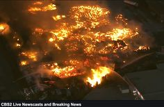 Flames and smoke billow from burning cardboard and wooden pallets at a recycling center. F...