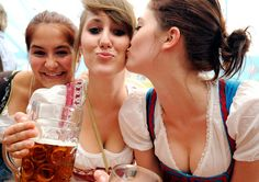 Young women in traditional dirndl dresses pose with beer mugs at the Oktoberfest beer festival Source: Boston.com #beer #oktoberfest #germany #dirndl #german boobs #women drinking beer #women and beer #beer girls