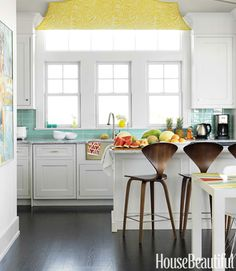 "Turquoise Tile  ""The kitchen has a classic, timeless quality,"" Berman says, ""with a few fun pops of color to keep it from being staid and predictable"" — like the fanciful valance in Arcadia Sulphur by Raoul Textiles and the Modwalls glass tile backsplash."