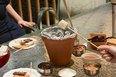 Fun party idea! A terracotta pot lined with aluminum foil, perched on a trivet and filled with hot coals from the grill makes a tabletop station for roasting marshmallows.