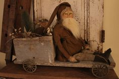 """Santa rides a wagon - BROWN -  Such down to earth, natural colors... 20''L x 16''H.  Wagon is made of 100 yr old wood with grey chippy paint weathered bare wood showing. grubby metal wheels and is filled with straw, a bottle brush tree, dried walnuts , tallow berries, and vintage ticking sack with tag saying """" for good children"""" The Santa wears an aged brown flannel coat, trimmed in pantry cloth, Vint brown/cream striped pants. Face is handsculpted clay. Signed, dated and one of a kind…"""