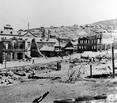 Pedestrians walk past the remains of Park Citys City Hall, with Marsac Mill in the background, after the 1898 fire. (Salt Lake Tribune Archive)