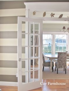 DIY striped wall - Paint adhesive contact paper your desired color, cut into desired strips, remove backing, and place on wall. Genius and removable. By City Farmhouse