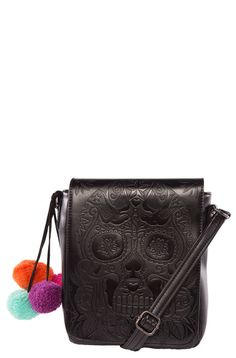 Make a lasting impression with this little black number! This handbag has a detailed embossed Calavera on the front and bright pom poms attached to the side _ a