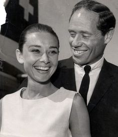 The actress Audrey Hepburn photographed with her husband Mel Ferrer (actor, dialogue coach and film director) during their arrival at the London Airport (known as Heathrow Airport since 1965) in London (England), from Zurich (Switzerland), on July 23, 1959.Audrey was wearing:Dress: Givenchy (sleeveless, of silk linen, belted at the waist with a sash in the same tissue, and buttoned with two buttons lined with the same tissue on each side, length below the knees, liner of silk, of his haute…