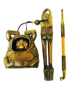 """19th C. Japanese two-piece tobacco container, wooden pipe with engraved metal mounts fitted into carved wooden holder in form of standing figure with arms upraised, connected by black string to hollow carved wooden container in form of squatting figure, cut out in stomach partially reveals moveable grimacing grotesque mask, mask moves up or down when string is pulled, missing white bead, expected surface wear, pipe and holder measures 8"""" l."""
