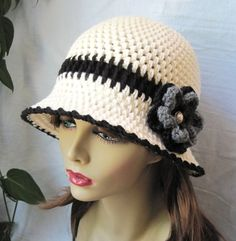 Chic Stylish Womens Hat. Off White Cloche Flapper. Flower. Black. Grey. Pearl Button. Hand-crocheted your choice of Acrylic yarn or Cotton, embellished with crocheted flower. The brim is malleable so you can style the hat as shown in the photos or any way you want. Makes unique wonderful gifts. Need this hat in another color and/or different flower? Please request for it. Please click on this to see more items http://www.jadeexpressions.etsy.com COLOR (S): Hat: Off White (Aran), Black…
