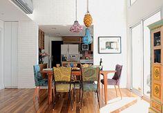 Integrada à cozinha pelo vão de 2,5 m x 2,5 m, a sala de jantar deste loft dúplex, em São Paulo, tem parede com tijolos de demolição pintados de branco e cadeiras estampadas coloridas. O projeto é da arquiteta Gabriela Marques
