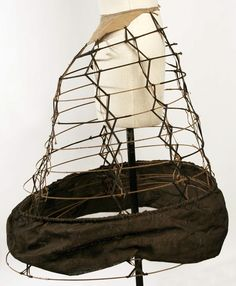 Cage crinoline with unusual design of narrow X tapes instead of wide vertical tapes. Met Museum dates to 1850s, but that's an awful lot of back thrust. [jrb]