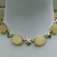 Vintage Thermoset Coro Necklace - 60s 6 pretty soft yellow thermoset moonglow lucite  cabachons intertwined with silvertone design. Signed Coro with the c copyright. Beautiful condition. Each cabachon disc measures 1 inch by 3/4 inch. 16 inches total. J hook closure. Vintage Coro Jewelry Necklaces