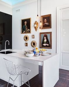 Eclectic kitchen by Ricardo de la Torre interior designer for Casa Decor 2012; I love the black glossy wall that reflects the room and the antique walls decorating a modern space