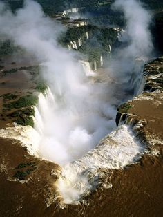 """Iguazu Falls: """"Great water"""" to the Guarani Indians, Iguazu Falls stretches for two miles (three kilometers) through the jungle near the border with Paraguay and Brazil. Parrots, toucans, jaguars, and tapirs share the surrounding orchid-dotted national park"""