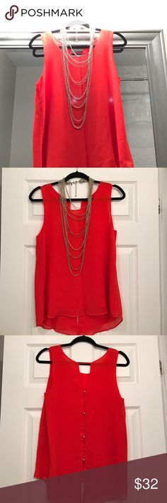 Lovely red blouse, silver accent buttons on back This lovely red sleeveless blouse features a simple front and lightly decorated back, with hooked silver buttons. Dress it up or dress it down! (note, necklace not included) Tops Blouses