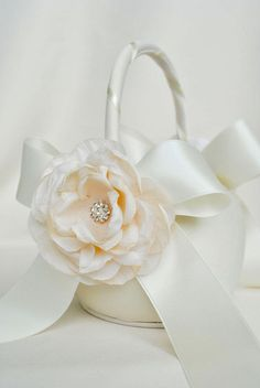 This dainty ivory flower girl basket is made with bridal satin. The basket features two luxurious ivory swiss bridal satin bows. At the center of Vintage Color Schemes, Hand Bouquet, Flower Girl Hairstyles, Flower Girl Basket, Satin Flowers, Rings For Girls, Pearl Flower, Flower Girl Dresses, Flower Girls
