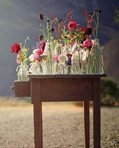 een oud tafeltje buiten zetten en wat flessen met bloemen erop