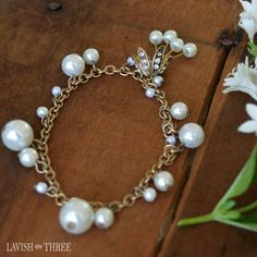 A multitude of pearls adorn our brushed gold vintage chain bracelet ~ additional pearls crown a golden lily inlaid with crystals.