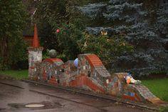 Für die Mauer verwendete Edgar Fischer verschiedene Steine, bunte Fliesen und Tonkugeln.
