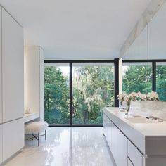 Duratherm windows provide a dramatic view of the ravine from the master bathroom. The clean lines of the Corian countertops, Dornbracht Deque faucets and cabinetry built by Stay-Straight Manufacturing allow the setting to take center stage.