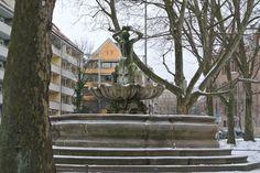 Tritonbrunnen, Nürnberg, Maxplatz; geschaffen 1689 von Johann Leonhard Bromig d.Ä. Ansicht nach Osten. Rückansicht. ... jetzt bei derzeit klirrender Januarskälte ist der Brunnen abgeschaltet, aber auch im Sommer ist der 30 cm hohe Spritzer nur noch ein kläglicher Rest der einst 4 Meter hohen Fontäne, die bildlich für den mächtigen Signalton dieser Hörner stand.