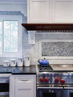 A wall of marble subway tile forms into a framed blue and brown mosaic tile backsplash that adds visual interest to this transitional kitchen. A blue tea kettle and red knobbed stove pop against the white cabinetry and black granite countertops.