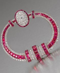 A rare Art Deco ruby and diamond fibula brooch, by Georges Fouquet, circa 1925. Of tapering annular form, the central row of calibré-cut rubies within borders of old brilliant and single-cut diamonds, with three central vertical accents of similarly cut stones and completed by a diamond and ruby bombé cluster, signed G. Fouquet and numbered, maker's marks for Georges Fouquet in two places, French assay marks, diameter 6.8cm. #ArtDeco #Fouquet #brooch