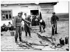 A German soldier orders Russian civilian`s to gather captured Soviet arm`s