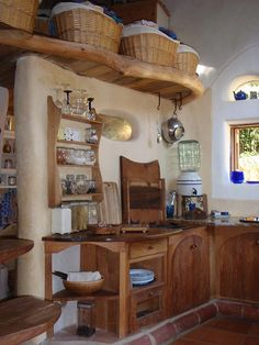 A darling kitchen in a a cob cottage.  I think if I ever built one of these I would have to go with blue and white in the kitchen instead of red and white.  I would just have to.
