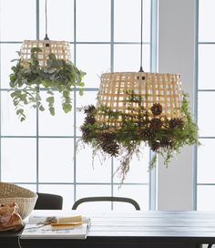 Two IKEA GADDIS baskets are decorated with greenery and pine cones and hung as a lamp.