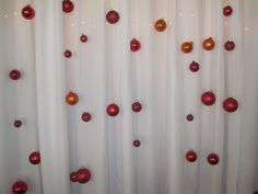 Christmas ornaments strung on fishing line at various heights for the head-table backdrop at out wedding :)