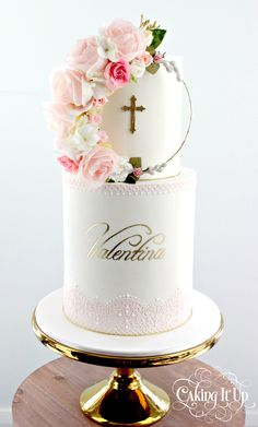 Two tier christening cake with double barrel tier featuring a handmade floral wreath and delicate hand painted name in gold. Edible lace and hand piped detail. www.facebook.com/cakingitup