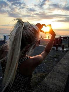 Take a picture wearing a: High ponytail, summer tank, and sunnies at the ocean and capture the sunset making heart with your hands!