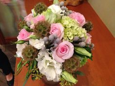 Roses, lisianthus, hydrangeas, and scabious pods.