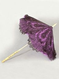 The purple parasol is made of handmade bobbin Chantilly lace & named this after the city of Chantilly, France.  Though called Chantilly lace, most of the lace which bore this name were actually made in Bayeux, France and Geraardsbergen (now in Belgium).  Chantilly lace is known for its fine, abundant detailing.  All parasols during this time period were delicate, fragile & expensive (Metropolitan Museum).