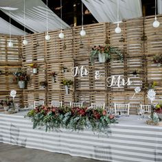 Reclaimed wooden pallets make a unique rustic backdrop at this protea-filled wedding. (Credit: Nikki Meyer)